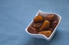 Muslim traditional basic iftar. A small bowl with dates on a blue fabric background, ramadan and iftar concept. This food is also a traditional snack in moroccan Stock Photos