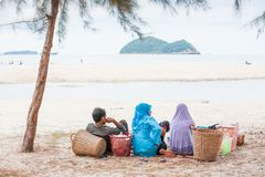 Muslim travelling, Rear view of Muslim family while picnicking. With wicker baskets on the beach. Islands background. Summer time. Soft sunlight. Songkhla Royalty Free Stock Photo