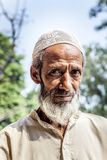 Muslim tribal man wearing. DELHI, INDIA - NOVEMBER 11, 2011: A muslim tribal man wearing traditional taqiyah (muslim cap) and galabia poses in the garden of Royalty Free Stock Photo