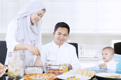 Muslim wife preparing meal for family. Muslim wife preparing meal for her family in dining table while her husband and child sitting in the kitchen Stock Image