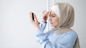 Muslim woman is applying compact powder looking at mirror.