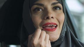Muslim woman applying red lipstick, bright makeup challenge to Islamic laws