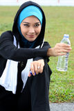 A muslim woman athlete holding a bottle of mineral. Water at stadium track Royalty Free Stock Images