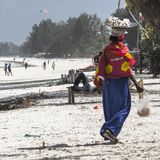 Muslim Woman on the beach. Woman with colorful clothes on the Beach in Zanzibar , Tanzania . Africa Royalty Free Stock Images
