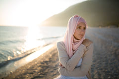 Muslim woman on the beach spiritual portrait. Humble muslim woman praying on the beach. Summer holiday, muslim woman walking royalty free stock image