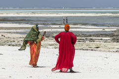 Muslim Woman on the beach. Two Women with colorful clothes wolking at  Michanwi Pingwe Beach in Zanzibar , Tanzania . Africa Stock Photography