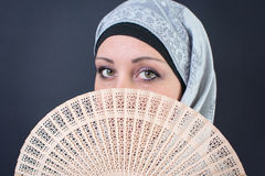 Muslim woman behind a hand fan Stock Photos