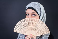 Muslim woman behind a hand fan Stock Photo