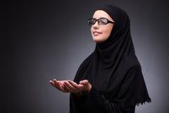 The muslim woman in black dress against dark background Stock Image