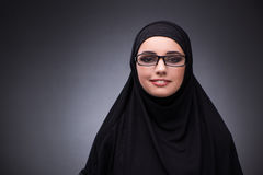 The muslim woman in black dress against dark background Stock Photography