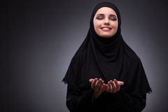 The muslim woman in black dress against dark background Stock Photo
