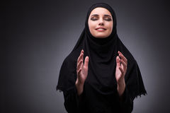 The muslim woman in black dress against dark background Stock Images