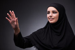 The muslim woman in black dress against dark background Royalty Free Stock Photos