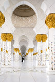 Muslim woman in black dress walking in a distance between white pillars. Muslim woman in black national dress walking in a distance between white pillars Royalty Free Stock Images