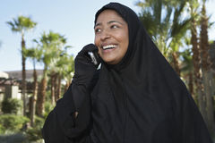 Muslim Woman In Black Hijab Using cell Phone Royalty Free Stock Photography