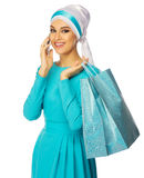 Muslim woman in blue dress with bags and phone Stock Photos