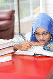 Muslim woman with a book. A muslim woman reading a book while looking at the book on the table Royalty Free Stock Photos