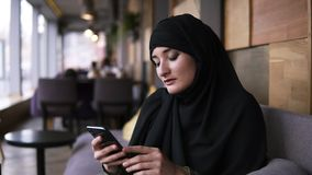 Muslim woman in cafe using her smartphone, chatting online browsing social media sharing lifestyle. Enjoying, relaxing stock video footage