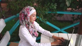 Muslim woman in cafe working on business with laptop stock video footage