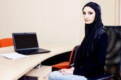 Muslim woman carrying the hijab while working on a laptop Stock Image