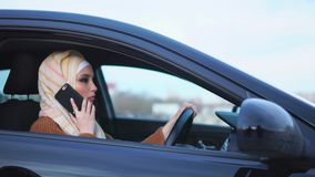 Muslim woman is on the cell in the car. Young Muslim woman driver communicating on mobile before going for a car ride on business. Lifestyle of modern Muslim stock video
