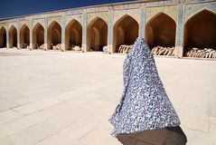 Muslim woman in a colorful chador going to a mosque Stock Photos