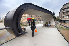 Muslim woman with colourful umbrella on Sestina lente, pedestrian bridge over Miljacka river. Royalty Free Stock Photos