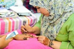 Muslim woman doing mehndi art design on hand royalty free stock photography