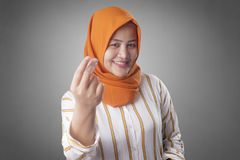 Muslim Woman Doing Money Gesture. Portrait of happy smiling Asian muslim woman doing cash, rich or money gesture adult advertising arab attractive beautiful stock photography