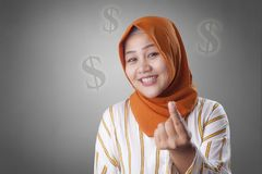 Muslim Woman Doing Money Gesture. Portrait of happy smiling Asian muslim woman doing cash, rich or money gesture adult advertising arab attractive beautiful royalty free stock images