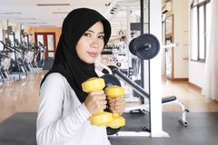 Muslim woman doing workout with two dumbbells. Muslim woman wearing sportswear and veil while doing workout with two dumbbells in the gym center Stock Photos