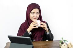 Muslim woman drinking coffee while working at home