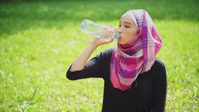 A Muslim woman drinks mineral water from a bottle in the parks on a summer day stock footage