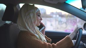 Muslim woman drives a car in the city. She uses cell phone. stock video footage