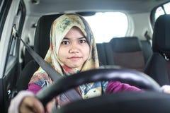 Muslim woman driving a car. Young muslim woman driving her car Stock Photo
