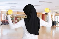 Muslim woman exercising with two dumbbells. Rear view of Muslim woman exercising with two dumbbells while standing in the fitness center Stock Images