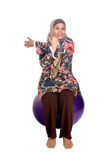 Muslim woman on fit ball. While stretching her tricep as part of healthy lifestyle concept Stock Images