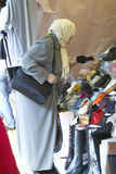 Muslim Woman at flea market shopping for shoes, Paris, France Royalty Free Stock Photography