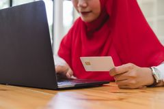 Muslim woman hands holding credit card and using laptop for online shopping. stock photography