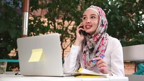 Muslim woman having business talk on mobile stock video footage