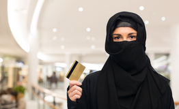 Muslim woman in hijab with credit card over white. Finances and people concept - muslim woman in hijab with credit card over shopping center background Stock Image