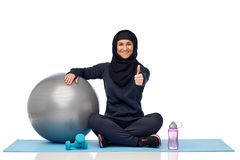 Muslim woman in hijab with fitness ball and bottle Royalty Free Stock Photos