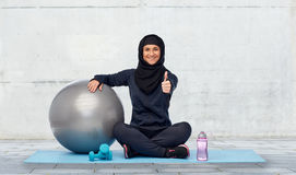 Muslim woman in hijab with fitness ball and bottle Royalty Free Stock Images