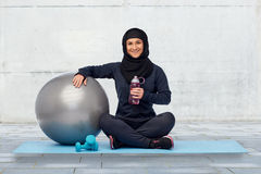 Muslim woman in hijab with fitness ball and bottle. Sport, fitness and people concept - happy smiling muslim woman in hijab with exercise ball, dumbbells and Stock Image