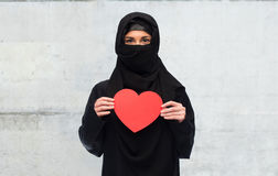 Muslim woman in hijab holding red heart Stock Photo