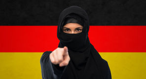 Muslim woman in hijab pointing finger to you. Immigration and people concept - muslim woman in hijab pointing finger to you over german flag background Royalty Free Stock Images