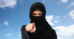 Muslim woman in hijab pointing finger to you. Religious and people concept - muslim woman in hijab pointing finger to you over blue sky and clouds background Royalty Free Stock Photos