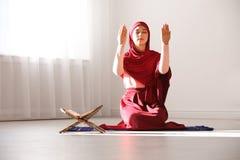 Muslim woman in hijab praying. On mat indoors royalty free stock image