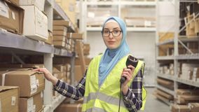 Muslim in hijab shop worker with barcode scanner. Muslim woman in hijab shop worker with barcode scanner looking at the camera stock footage