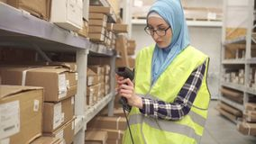 Muslim in hijab store worker conducts accounting using barcode scanner. Muslim woman in hijab store worker conducts accounting using barcode scanner stock video
